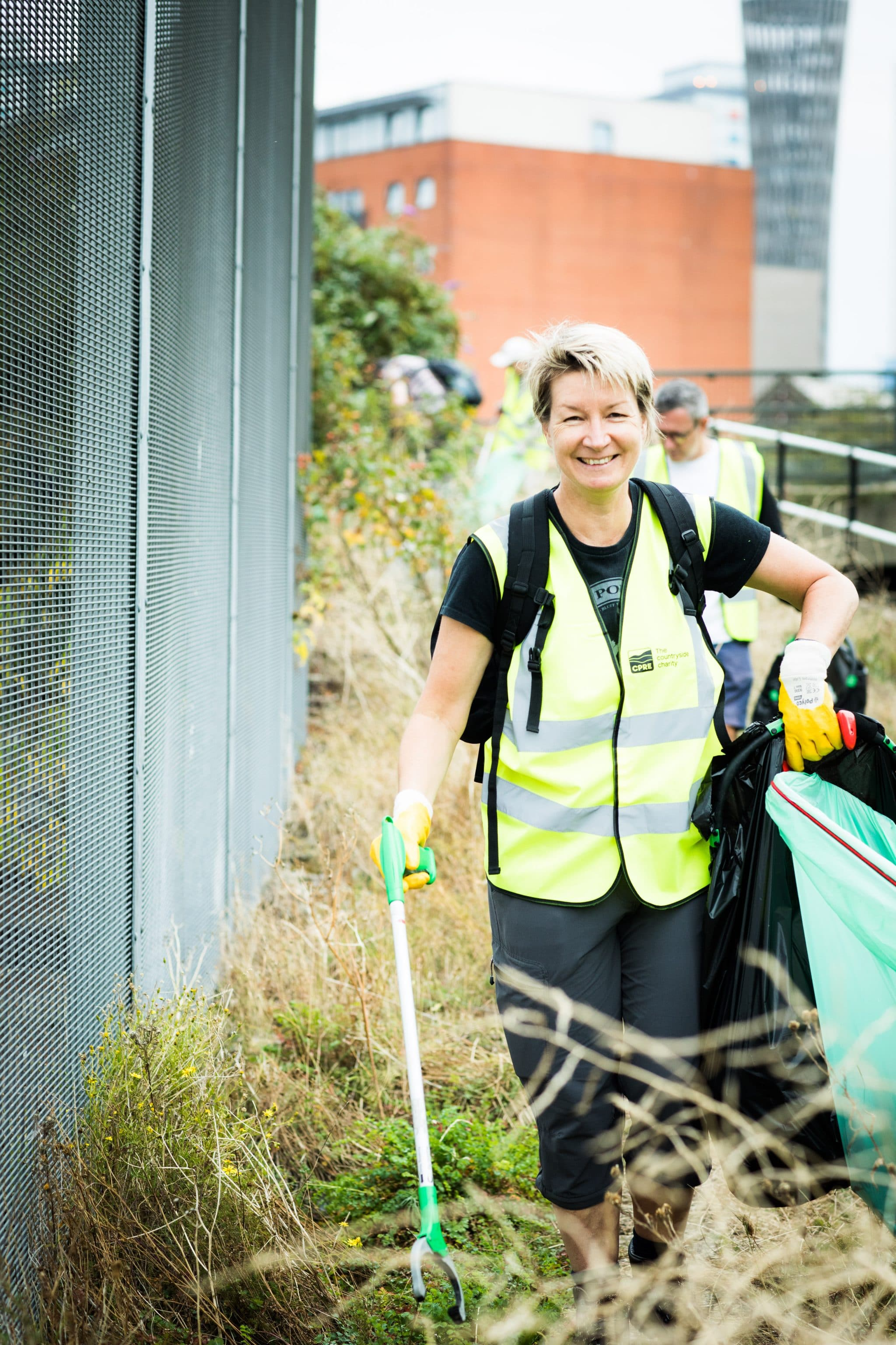 Blonde happy woman litter picking wearing hi vis jacket