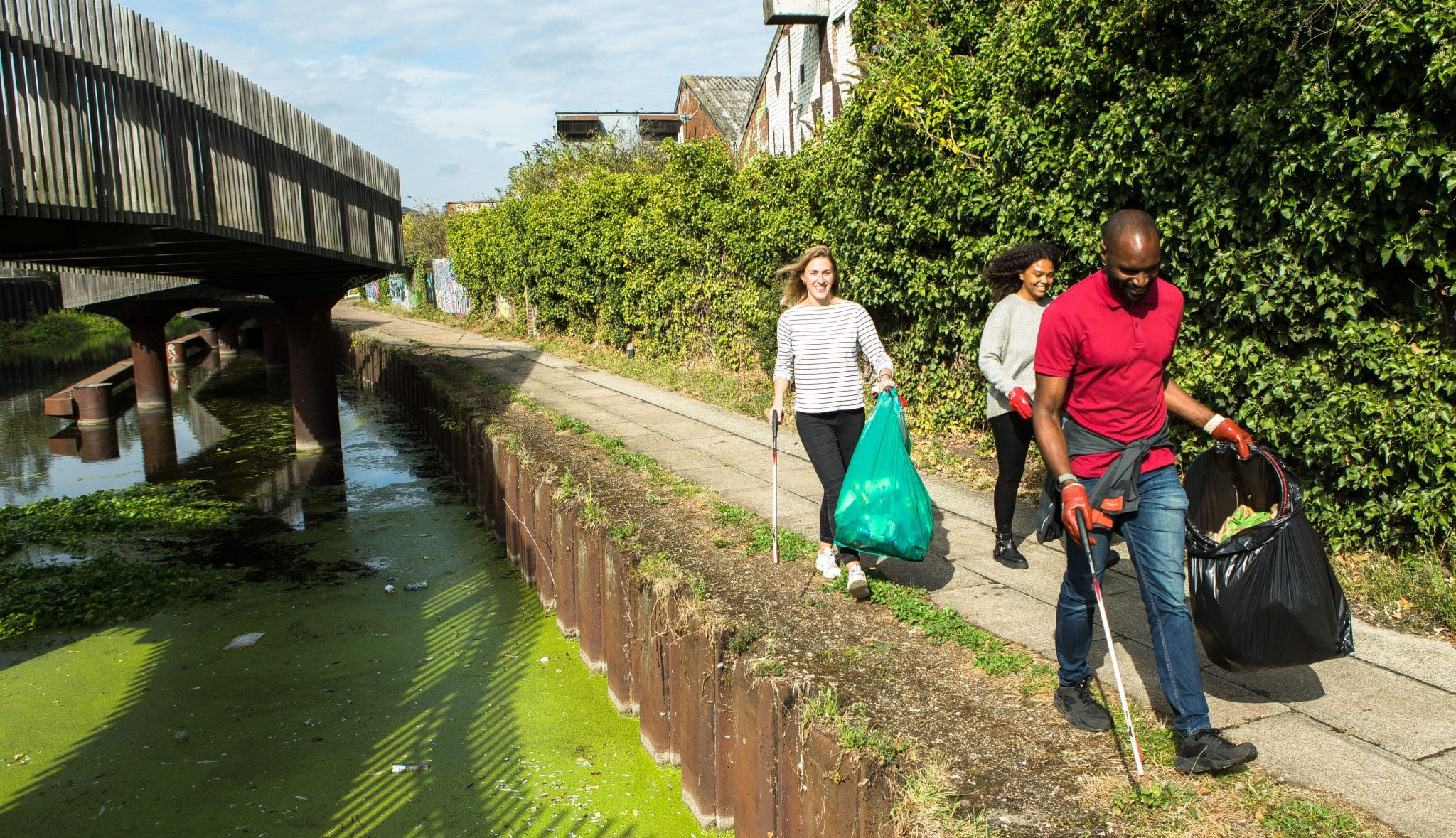 Three people man and two women litter picking along urban canal